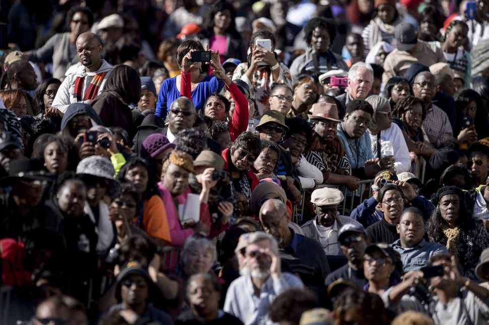 People listen as US President Barack Obama speaks at the Edmund Pettus Bridge on March 7, 2015 in Selma, Alabama.