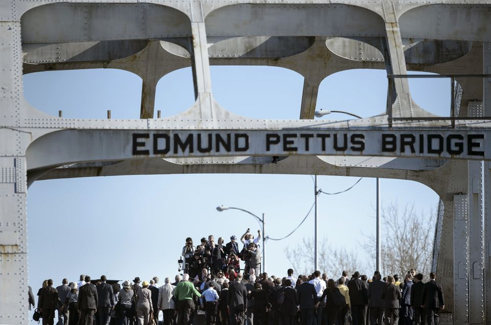 A large group including US President Barack Obama cross the Edmund Pettus Bridge on March 7, 2015 in Selma, Alabama.
