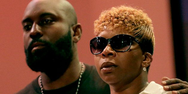 Parents of Michael Brown, Michael Brown Sr. and Lesley McSpadden listen to a speaker during a rally, Sunday, Aug. 17, 2014, f