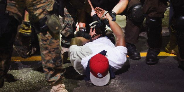FERGUSON, MO - AUGUST 19:  Police arrest a demonstrator protesting the killing of teenager Michael Brown on August 19, 2014 i