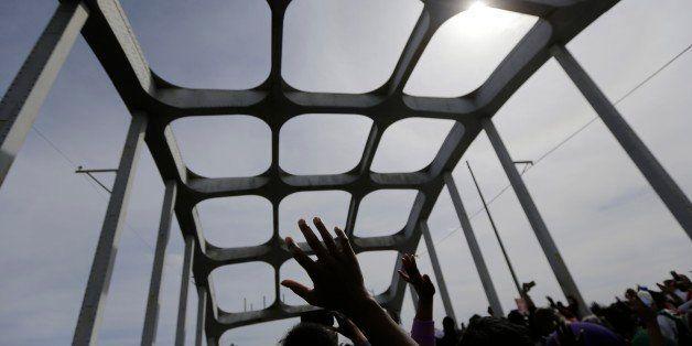 Crowds of people take a symbolic walk across the Edmund Pettus Bridge, Sunday, March 8, 2015, in Selma, Ala. This weekend mar
