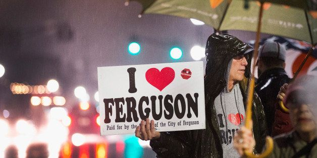 FERGUSON, MO - MARCH 13:  Demonstrators voice support for the Ferguson mayor and police outside the police station, on March
