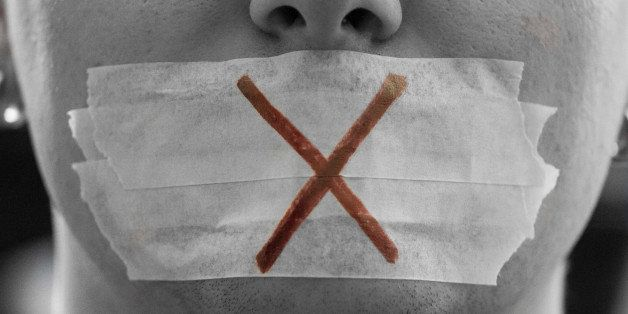 'A male face with a taped mouth and a red cross on it symbolizing censorship.Censorship is all around.Freedom of speech is th