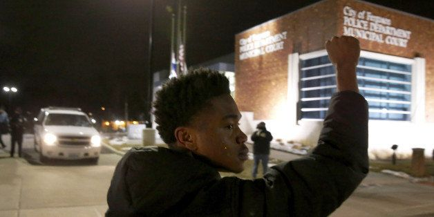 Clifton Kinnie joins protesters as they block traffic on the street outside the Ferguson, Mo., police department Wednesday, M