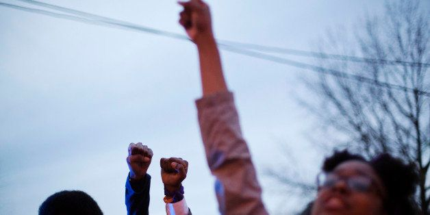 Protesters raise their fists during a demonstration against the shooting death of Anthony Hill by a police officer, Wednesday