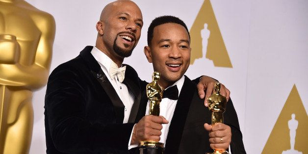 """Common, left, and John Legend pose in the press room with the award for best original song in a feature film for """"Glory"""""""