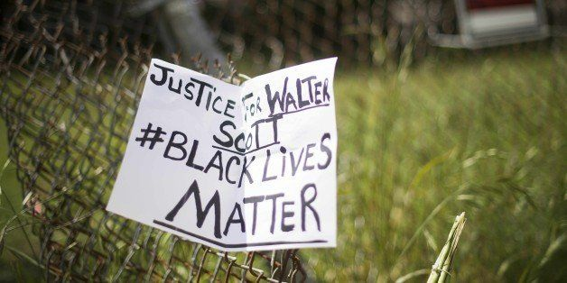 A placard is tied to a fence outside the vacant lot where Walter Scott, the 50-year-old man who was fired at eight times was