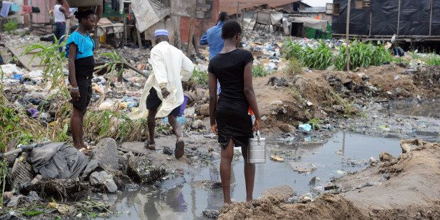 People walk past shanty homes at Badia East slums in Lagos on August 12, 2013. Forced evictions in Nigeria's largest city Lag