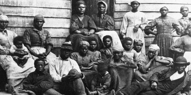 Portrait of Civil War 'contrabands,' fugitive slaves who were emancipated upon reaching the North, sitting outside a house, p