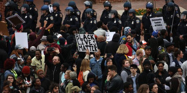BALTIMORE, MD - APRIL 25: Protesters hold signs as they stand off with the police at Camden Yard during a march in honor of F
