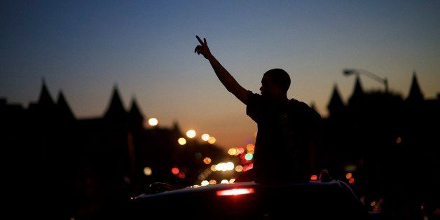 BALTIMORE, MD - APRIL 28:  Young people in cars drive towards a phlanx of Baltimore riot police honking their horns and raisi