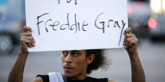 Lee Martel, 27, holds a sign during a protest, Tuesday, April 28, 2015, in Los Angeles following the funeral of Freddie Gray,