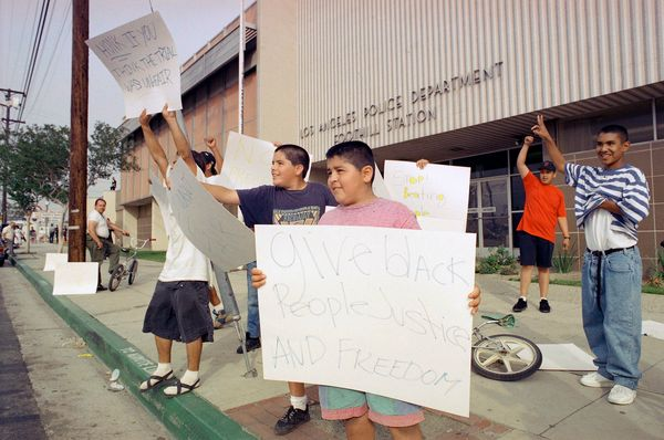 Luis Bernal, 13, center, and his brother, Juan, behind left, wave placards protesting police brutality outside the Foothill D