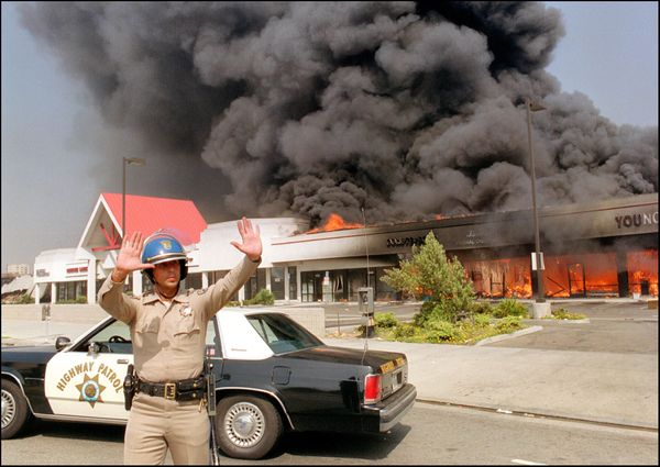 A California Highway patrolman directs traffic around a shopping center engulfed in flames in Los Angeles, on April 30, 1992.