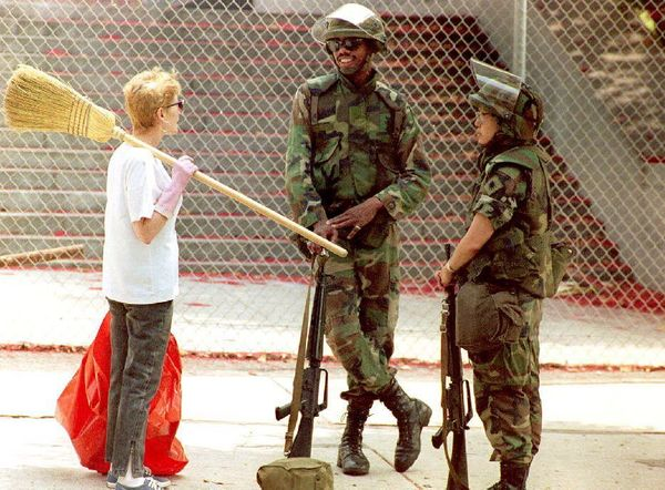 Two members of the National Guard talk to a volunteer clean-up worker May 3, 1992 on a street in south central Los Angeles as