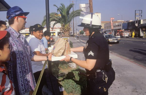 Community members giving lunch to policeman, South Central Los Angeles, California (Photo by Visions of America/UIG via Getty