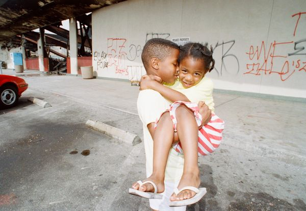 Donell Moore, 7, carries his 3-year-old sister, Deshe, in front of a graffiti-sprayed wall of a burned-out drugstore in Los A