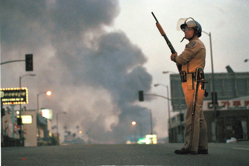 A California Highway Patrol officer stands guard at Ninth Street and Vermont Avenue in Los Angeles as smoke rises from a fire