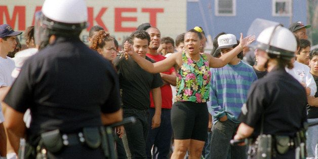 A woman yells at Los Angeles police officers who stand guard outside a shopping center, 30 April 1992, in Los Angeles. The ac