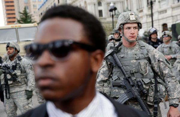 A member of the National Guard stands outside Baltimore City Hall as marchers protest the death of Freddie Gray, Wednesday, A