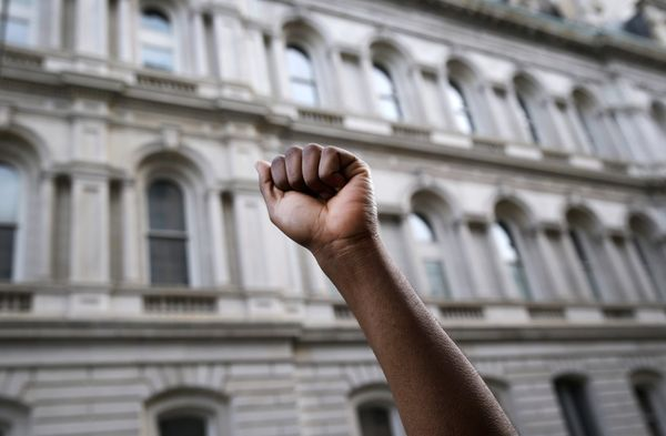A protestor raises his fist outside of Baltimore City Hall as marchers protest the death of Freddie Gray, Wednesday, April 29