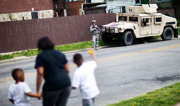 A member of the National Guard stands watch outside a neighborhood next to the Mondawmin Mall, scene of some of Monday's riot
