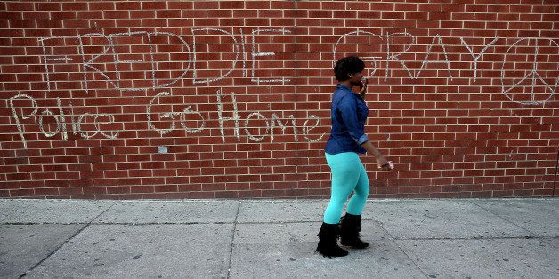 BALTIMORE, MD - MAY 02: A woman walks by a tagging that reads 'Freddie Gray...Police Go Home' a day after Baltimore authoriti
