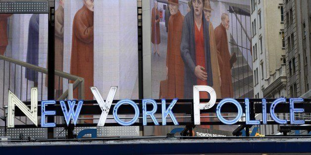 The neon sign at the New York Police Department Times Square Station, shows an image of 'The Subway, 1950' by George Tooker,