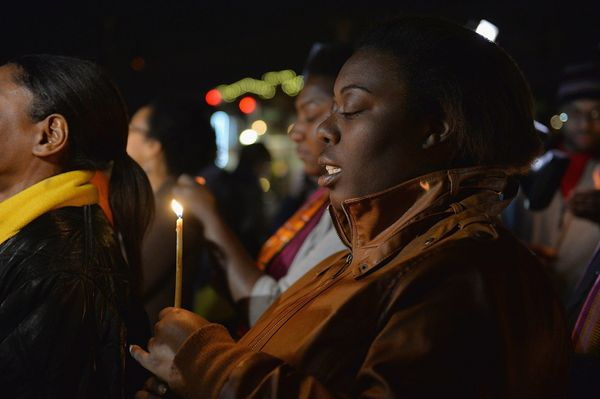 A woman participates in a candlelight memorial vigil near the Ferguson Police Department in Ferguson, Missouri on March 12, 2