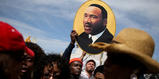 SELMA, AL - MARCH 08:  A marcher holds a picture of Dr. Martin Luther King Jr. before walking across the Edmund Pettus Bridge