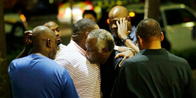 Worshippers embrace following a group prayer across the street from the Emanuel AME Church following a shooting Wednesday, Ju