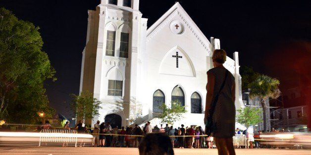 A woman pauses in respect as she passes next to Emanuel AME Church in Charleston, South Carolina on June 18, 2015.  Police ca