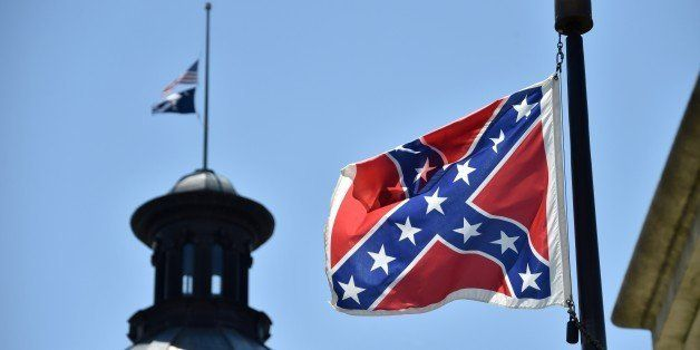 The South Carolina and US  flags are seen flying at half-staff behind the Confederate flag erected in front of the State Cong