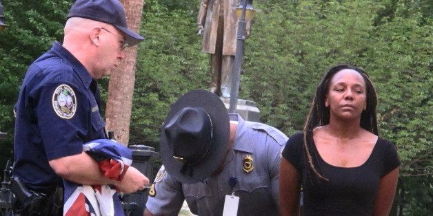 Bree Newsome of Charlotte, N.C., right, is taken into custody after she removed the Confederate battle flag from a monument i