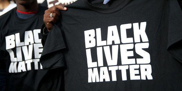 SAN FRANCISCO, CA - DECEMBER 18:  A protestor holds a black lives matter t-shirt during a 'Hands Up, Don't Shoot' demonstrati