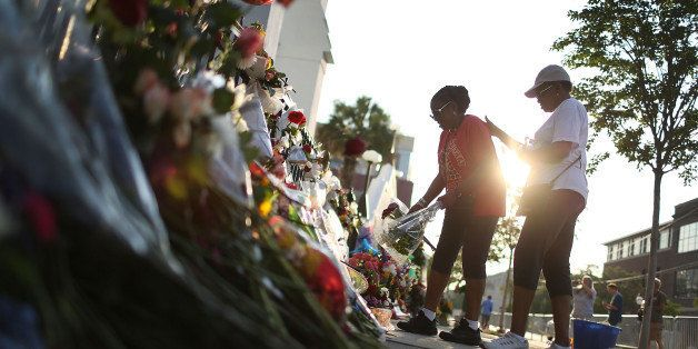 CHARLESTON, SC - JUNE 20:  Carolyn Wright-Porcher (L) and her sister Cynthia Wright-Murphy lay flowers on the memorial in fro