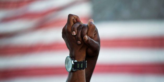People join hands against the backdrop of an American flag as thousands of marchers meet in the middle of Charleston's main b