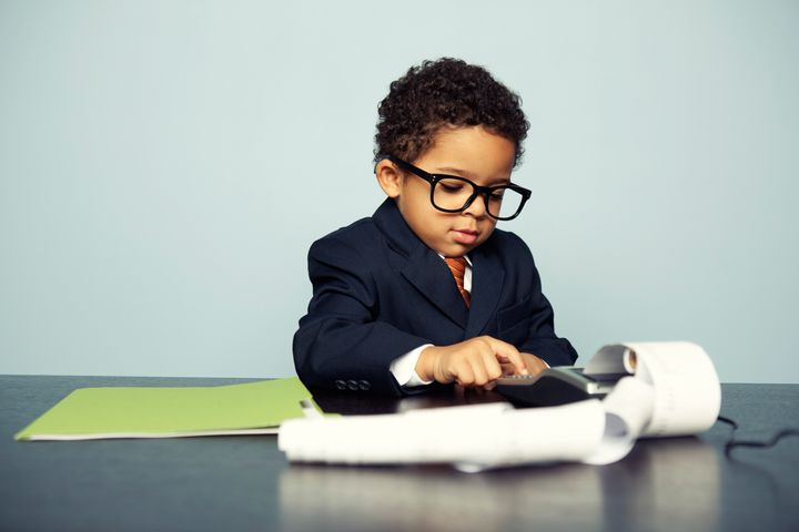 Portrait of a little boy financial advisor hard at work. How are your finances looking?