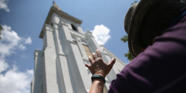 CHARLESTON, SC - JULY 17:  People pray in front of the Emanuel AME Church on the one-month anniversary of the mass shooting o