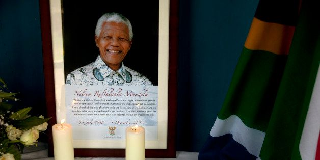 Candles burn in front of a photo of late Nelson Mandela at Kilimani Primary School in Nairobi, Kenya, Monday, Dec. 9, 2013.