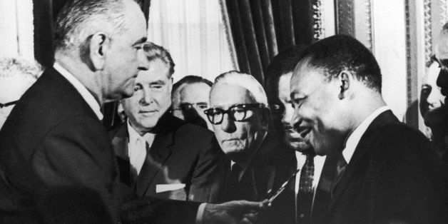 U.S. President Lyndon B. Johnson hands a pen to civil rights leader Rev. Martin Luther King Jr. during the the signing of the