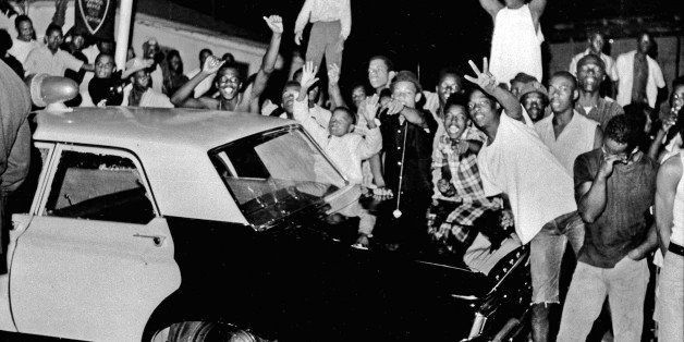FILE - In this Aug. 12, 1965 file photo, demonstrators push against a police car after rioting erupted in the Watts district