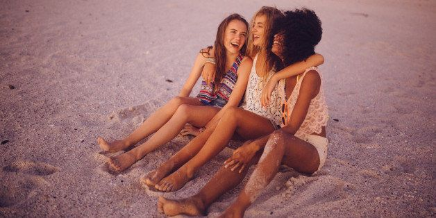 Mixed racial group of girl friends sitting on the beach at sunset hugging and laughing