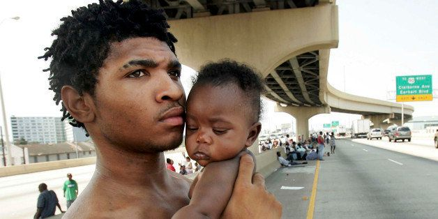 NEW ORLEANS - AUGUST 31:  Daryl Thompson holds his daughter Dejanae, 3-months, as they wait with other displaced residents on