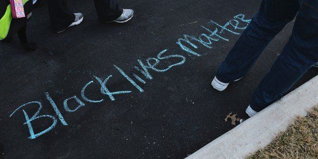 'Black Lives Matter' is drawn on the ground in chalk as protesters demonstrate against racism in the 'Reclaim MLK' march Janu