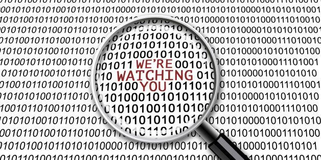 A magnifying glass on binary codes with the words 'We're watching you' in focus
