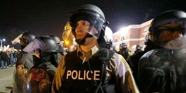 FILE- In this Nov. 25, 2014 file photo, police watch the street as protesters gather outside the Ferguson Police Department i