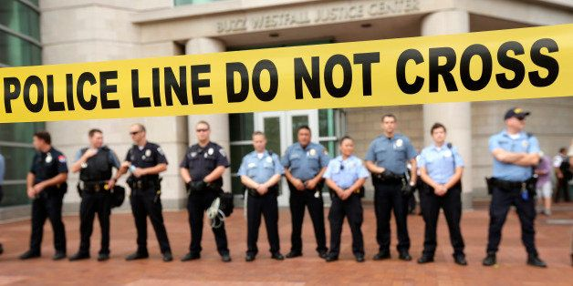 Police guard the entrance to the Buzz Westfall Justice Center in Clayton, Mo., Wednesday, Aug. 20, 2014, where a grand jury i