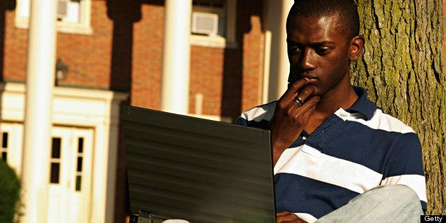 a black college student on his laptop on campus.