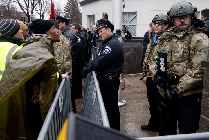 A Black Lives Matter supporter, left, talks to Minneapolis police guarding the Fourth Precinct entrance, Wednesday, Nov. 18,